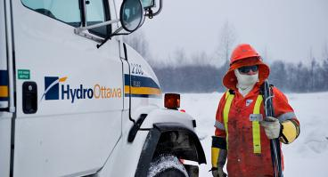 Hydro Ottawa crew member walking toward Hydro Ottawa-branded truck in winter
