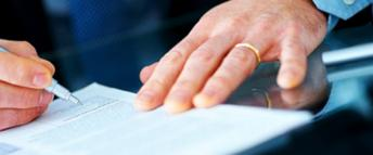 Close up of a man's hands as he signs a document