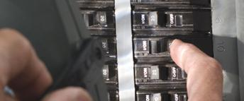 A person flipping a switch on a circuit breaker