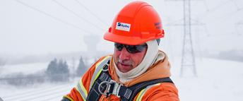 A Hydro Ottawa power line maintainer repairing power lines on a cold, winter day