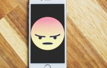 Cell phone with an unhappy face on the screen